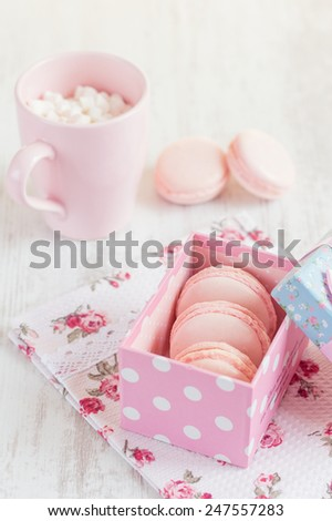 Pink macaroons in gift box with cup of coffee. Pastel colored - stock photo