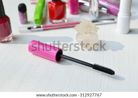 Pink mascara stick, eyeliner, lipstick, pencil and other cosmetics on the white dressing table - stock photo