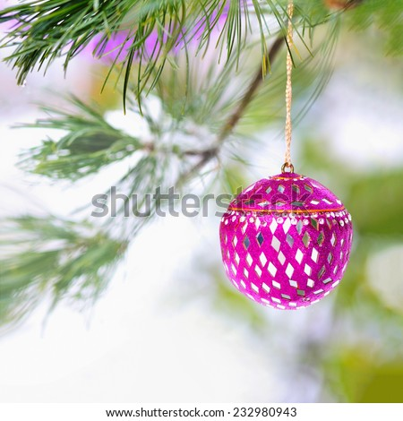 Pink mirrored Christmas ornament and pink garland hang from the boughs of a pine tree with snow and copy space for a Christmas holiday background, greeting card or other text. Square format - stock photo