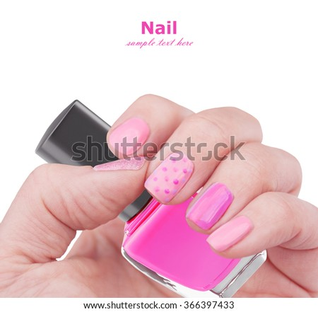 Pink nail art manicure isolated on white background with sample text. Bright manicure with painted dots. Hand with bottle of nail polish. Beauty salon trendy manicure.  - stock photo