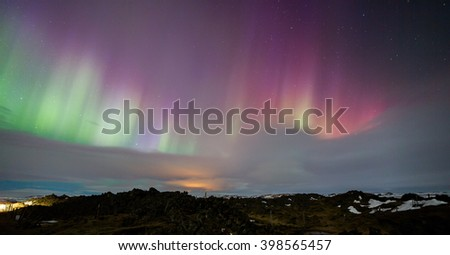 Pink Northern Lights above Iceland landscape - stock photo