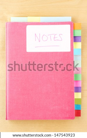 Pink notebook on a light wood background.  White 'Notes' label on cover, three tab dividers along top edge and fifteen down right side.  Eighteen tabs in total, left blank to provide space for text. - stock photo
