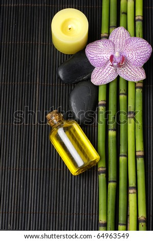 Pink orchid and parfume bottle and yellow candle on mat - stock photo