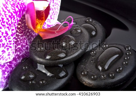 Pink orchid and stones for massage on black background - stock photo