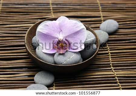 Pink orchid and stones in bowl on bamboo mat - stock photo