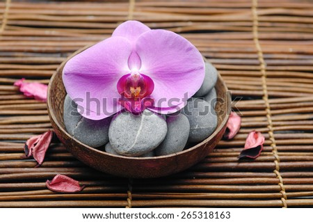 Pink orchid with gray stones in wooden bowl on mat  - stock photo