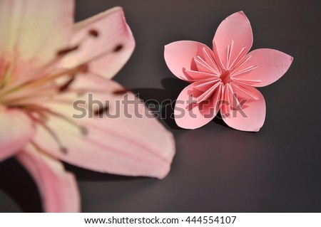 Pink origami flower along with a real pink lily blossom. - stock photo