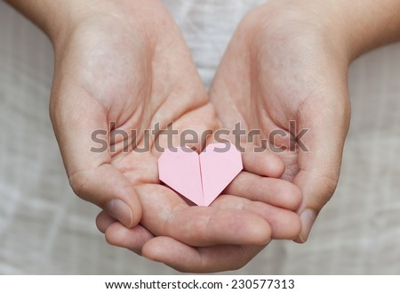 Pink origami heart in human hands - stock photo