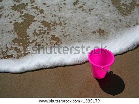 Pink pail sitting in the sand at the beach as a wave approaches. - stock photo