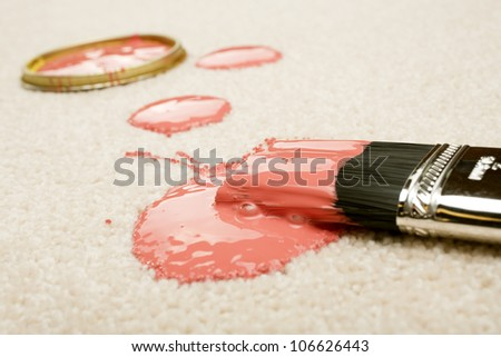 Pink paint spilled on cream coloured carpet with brush. - stock photo