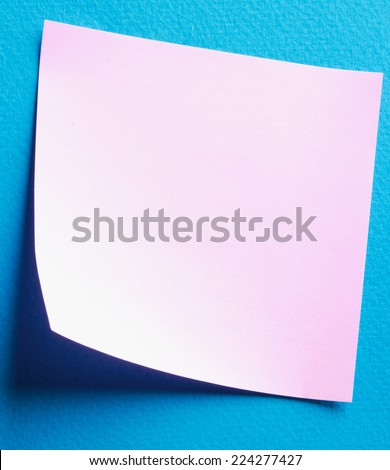 Pink paper note on blue background - stock photo