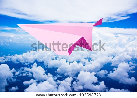Pink paper plane flying against blue sky - stock photo