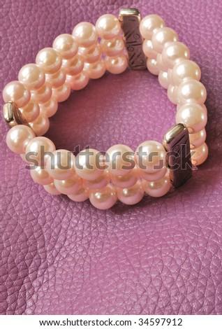 Pink pearl bracelet on light violet leather - stock photo