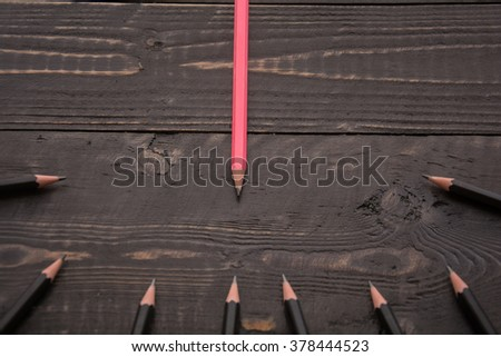 Pink pencil stands out from the crowd of other black pencils on a wood background.Concept of business success.Strategy,uniqueness,independent,dissent,think differently - stock photo