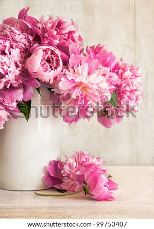 Pink peonies in vase on wood background - stock photo