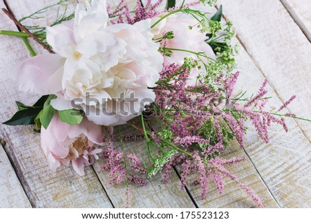 Pink peony and wild flowers on wooden background. - stock photo
