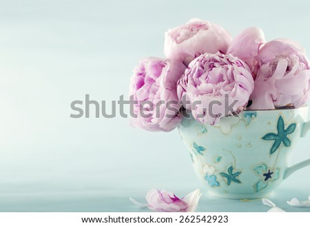Pink peony flowers in a decorative cup on light blue vintage background with hazy vintage editing - stock photo