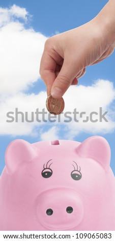 Pink pig money box with hand depositing British pound coin - stock photo