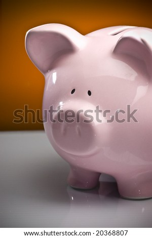 Pink piggy bank against white and orange background - stock photo