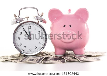 Pink piggy bank beside alarm clock on dollars on white background - stock photo