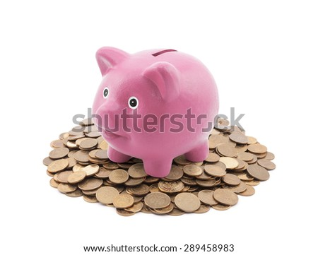Pink piggy bank on a pile of coins  - stock photo