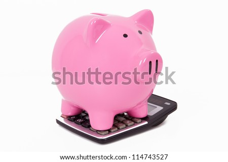 Pink piggy bank on calculator, isolated on white background. - stock photo