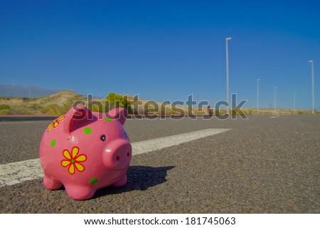 Pink Piggy Bank on the Asphalt Street - stock photo