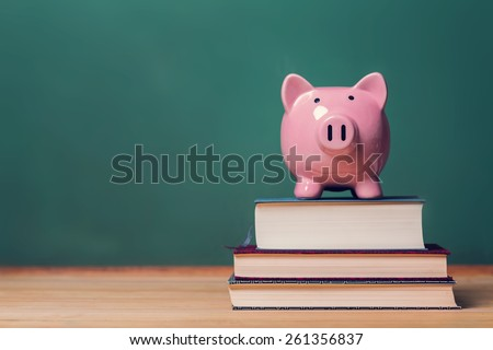 Pink Piggy bank on top of books with chalkboard in the background as concept image of the costs of education  - stock photo