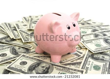 pink piggy bank sitting on top of hundred dollar bills - stock photo