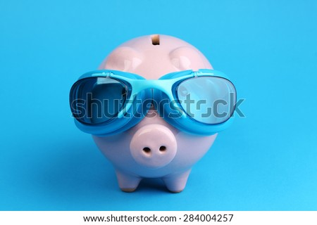 Pink piggy bank with blue swimming goggles on blue background like swimmer - stock photo