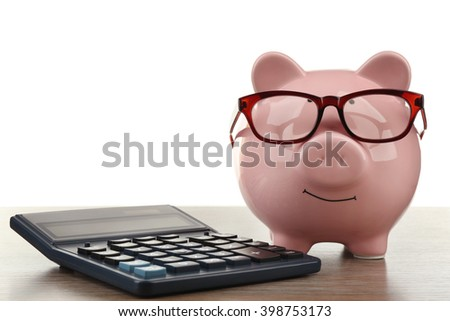 Pink piggy bank with glasses and calculator on white background - stock photo