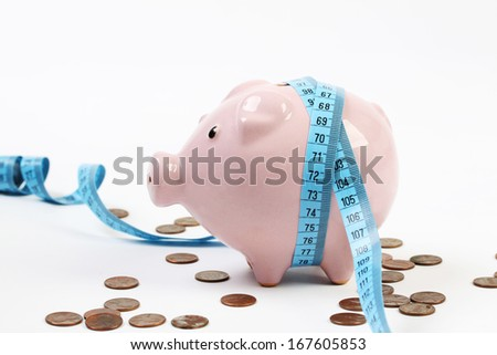 Pink piggy bank with measuring-tape and around a lot pennies on white background - stock photo