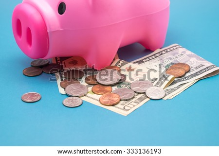 Pink piggy bank with us dollars and coins for financial symbol with selective focused point - stock photo