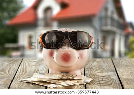 pink piggybank on top and sunglases money and free space  - stock photo