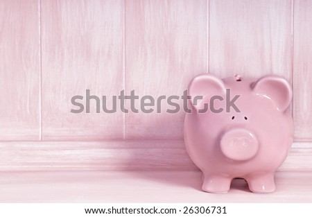 Pink piggybank with brushed timber background.  Lots of copy-space. - stock photo