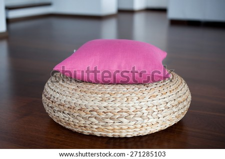 Pink pillow on pouffe in white interior  - stock photo