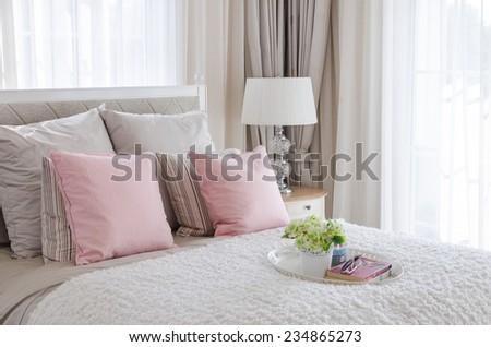 pink pillows on bed with tray of flower at home - stock photo