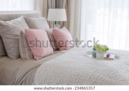 pink pillows on bed with white tray of flower at home - stock photo