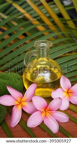 Pink plumeria and aromatic massage oil - stock photo