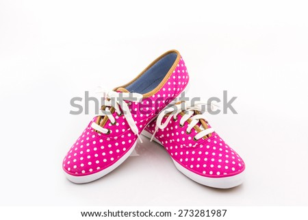 Pink polka dot sneakers on a white background. Canvas Shoe.  - stock photo