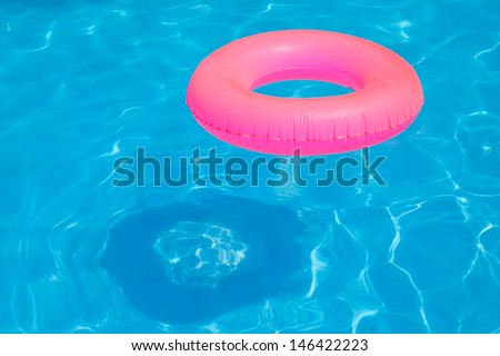 Pink pool float, pool ring in cool blue refreshing blue pool - stock photo