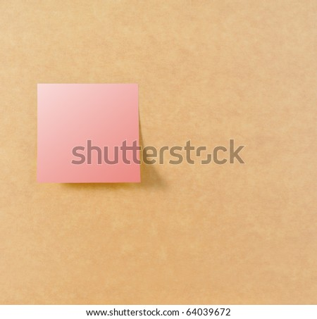Pink post it on left of brown board texture - stock photo