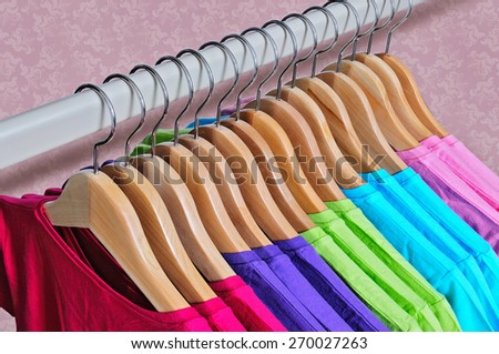 Pink, purple, crimson, bright green and turquoise women's T-shirts hanging on wooden hangers on pink background - stock photo