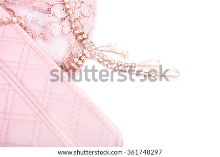 Pink purse and jewelry with crystals on a white background - stock photo