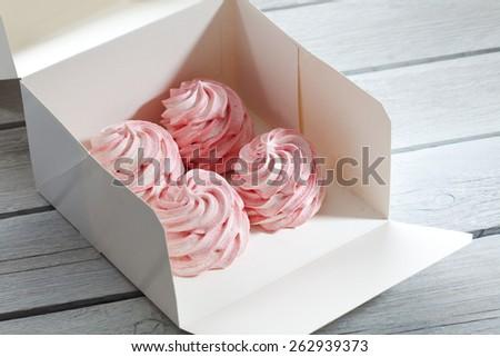 Pink raspberry meringue in a folded box - stock photo