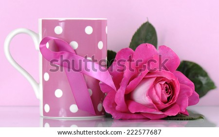 Pink Ribbon Charity for Womens Breast Cancer Awareness fund raising with pink polka dot coffee mug and rose against a pink background - stock photo
