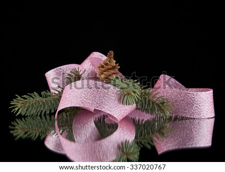 pink ribbon, christmas tree branch and pine cone on a black background - stock photo