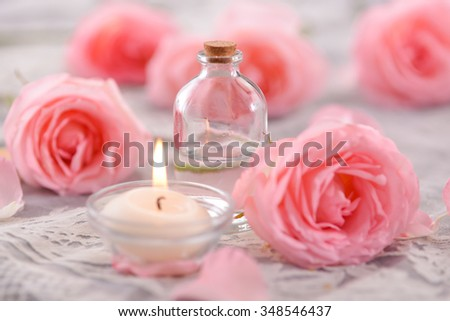 Pink rose petals and rose with candle on lace - stock photo
