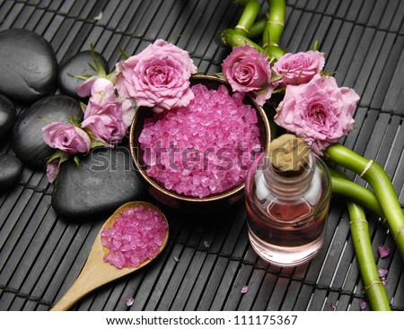 Pink rose with salt in bowl and massage oil ,grove on green mat - stock photo