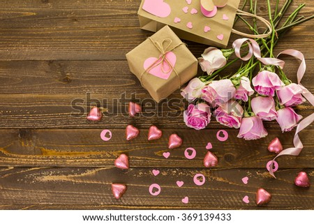 Pink roses and gift wrapped in recycled paper on rustic wood table. - stock photo